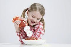 Girl (4-5) pouring ketchup on spagetti - stock photo