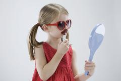 Girl (4-5) wearing sunglasses and playing with lipstick Stock Photos