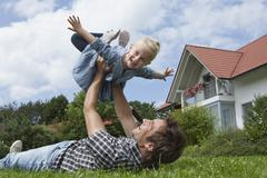 Germany, Munich, Father playing with daughter (2-3 Years) in garden Stock Photos
