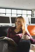 Businesswoman in office holding cup and newspaper, smiling, portrait Stock Photos