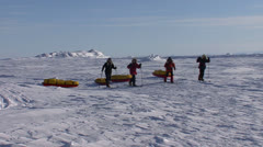 Stock Video Footage of An Arctic expedition moves across frozen tundra on cross country skis towing