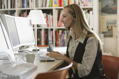 Young woman in office with headset using computer, portrait - stock photo