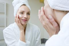 Young woman applying beauty cream Stock Photos
