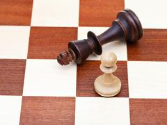 standing and fallen chess king and pawn - stock photo