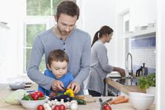 Father and son (2-3 Years) chopping pepper and mother in background - stock photo