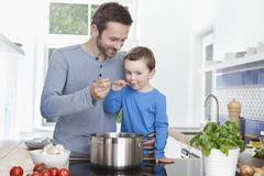 Germany, Munich, Father feeding meal to son (2-3 Years) - stock photo