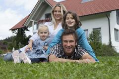 Stock Photo of Germany, Munich, Family in front of house, smiling, portrait