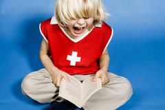Boy reading book, screaming - stock photo