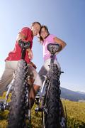 young couple on bicycle, smiling, low angle view, portrait - stock photo