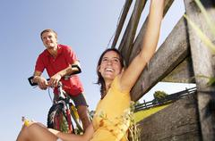 Couple having a rest, woman leaning on wooden railing Stock Photos