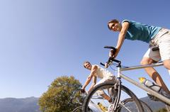 young couple riding mountain bike, smiling, low angle view - stock photo