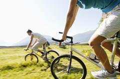 Young couple riding mountain bike, side view, (blurred motion) Stock Photos