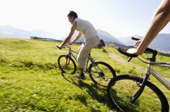 young couple riding mountain bike, side view, (blurred motion) - stock photo
