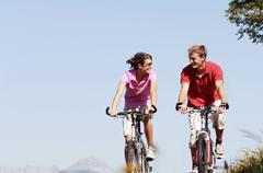 Young couple riding mountain bike, face to face, smiling Stock Photos