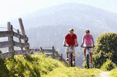 young couple riding mountain bike by wooden fence, mountains in background - stock photo