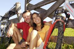 couple sitting in meadow, leaning on wooden railing - stock photo