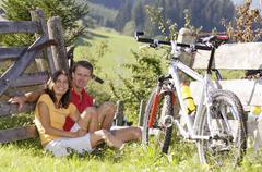 young couple sitting in meadow with mountain bike, leaning on wooden fence - stock photo
