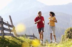 Stock Photo of young couple jogging by wooden fence, mountains in backgrounds