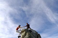Couple climbing on summit Stock Photos