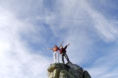 young couple standing on mountain peak, arms out, low angle view - stock photo