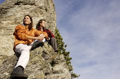 Young couple relaxing on mountain peak, low angle view Stock Photos