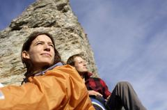 young couple resting in mountains, focus on woman, low angle view - stock photo
