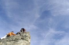 young couple climbing on mountain peak, low angle view - stock photo