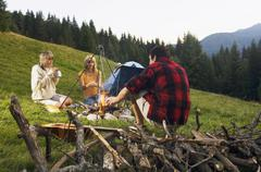 three young poeple sitting around campfire - stock photo