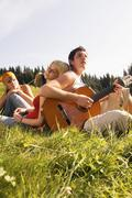 Young people in meadow, man playing guitar, low angle view Stock Photos
