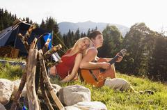 nuori pari istuu niityllä, mies kitaransoiton - stock photo