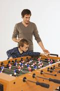 Father and son (4-5) playing tabletop soccer - stock photo