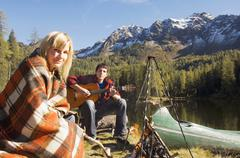Young couple camping at lake, man playing guitar Stock Photos