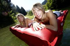 Young couple lying on air mattress Stock Photos