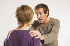 Father and son (13-14), man looking frightened - stock photo