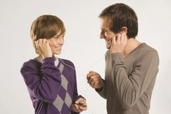 Father and son (13-14) listening to MP3 player Stock Photos