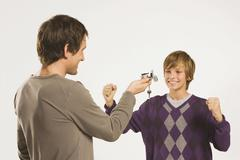 Father and son (13-14), Man handing bike key to boy - stock photo