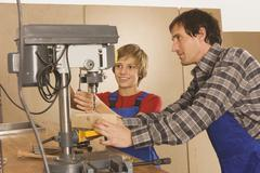 Germany, father and son , Working on drill machine Stock Photos