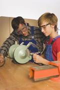 Germany, father and son, Working on grinding machine Stock Photos