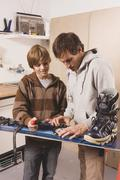 Germany, father and son fixing snowboard, smiling Stock Photos