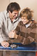 Germany, father and son fixing snowboard, smiling - stock photo