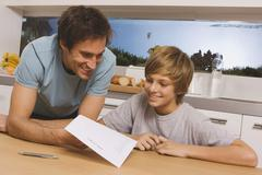 Father and son (13-14) looking at report card Stock Photos