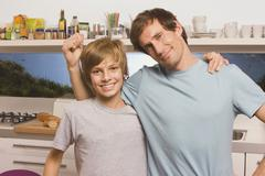 Father and son (13-14) smiling, Man gesturing, portrait - stock photo
