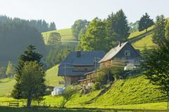 Germany, Black forest, Grange in hilly landscape - stock photo