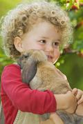 Blonde girl (4-5) with curly hair holding rabbit, portrait Stock Photos