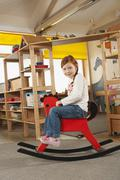 Germany, Girl (6-7) sitting on rocking horse, side view, portrait Stock Photos