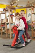 Germany, Two girls (4-5), (6-7) sitting on rocking horse, side view, smiling, Stock Photos