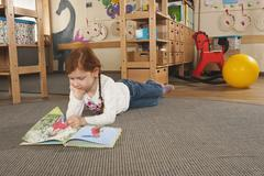 Germany, Girl (6-7) in nursery lying on carpet reading a book Stock Photos