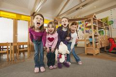 Germany, Children in nursery standing side by side screaming, portrait - stock photo