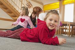 Germany, Children in nursery, girl (6-7) lying on floor, children in background - stock photo