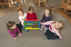Germany, Children in nursery holding letter board, elevated view - stock photo